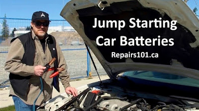 Steve with booster cables in hand under the hood of his Buick Century