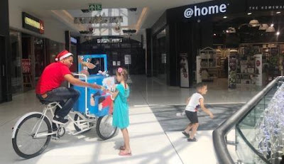 Elf on bicycle at Fourways Mall handing out crackers and popcorn