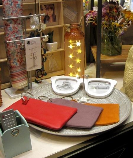 Bolsos cartera piel con anilla en rojo, lila y naranja, sobre plato decorativo