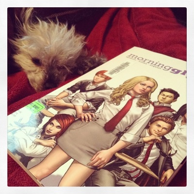 Murchie lays behind a trade paperback copy of Morning Glories. The cover features a group of mostly white young people wearing variations on the same school uniform: white shirt, red tie, greyish tan skirt or pants.
