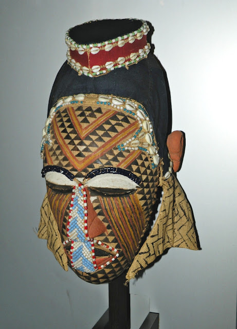 African wooden mask decorated with cowrie shells and beads