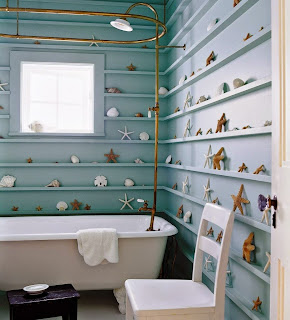 cool bathroom with nautical theme decorating on whole wall with blue shelving around white  tub with golden shower