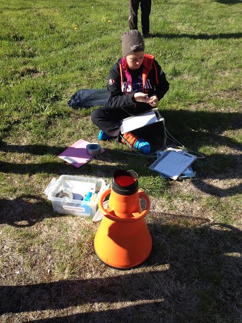 Henkilö istuu nurmikolla ja tarkastelee välineitä