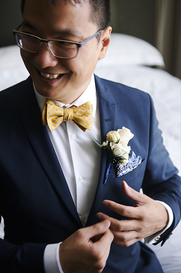 Groom attire details: navy suit, white shirt, yellow and blue bow tie