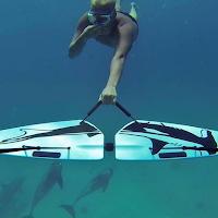 Un plongeur accroché à une aile sous marine Subwing tirée par un bateau.