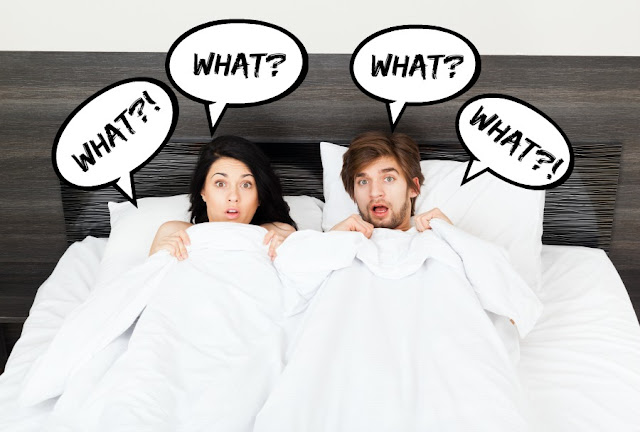 Man and woman in bed surprised.