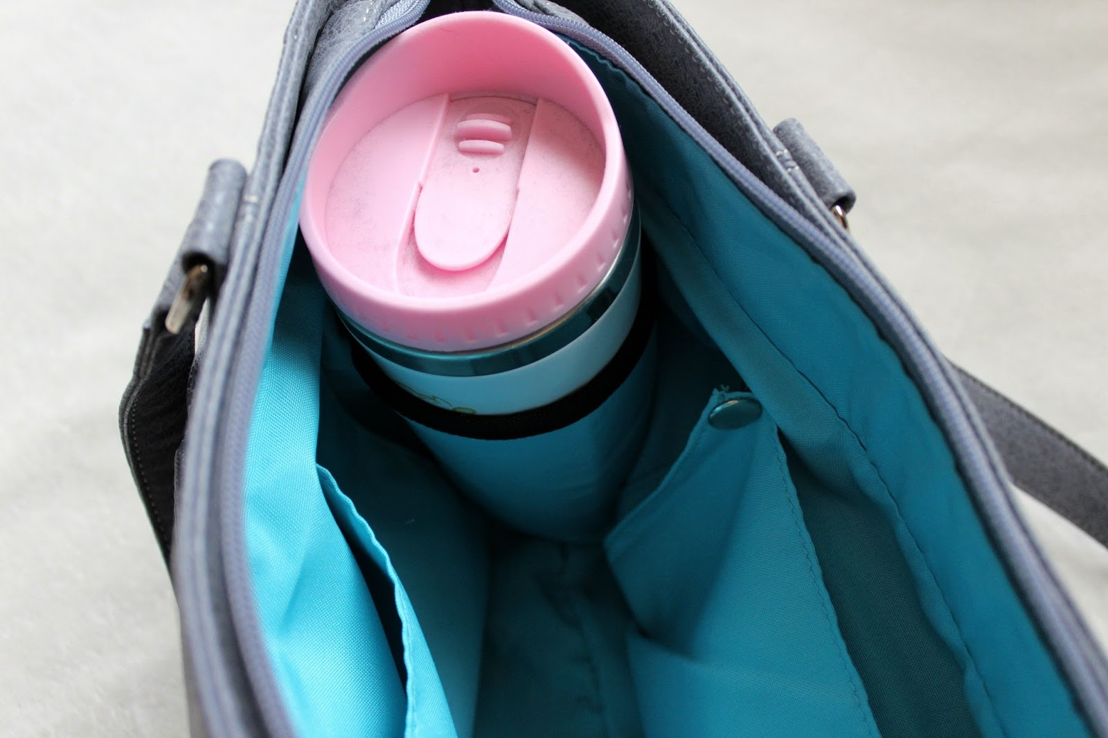 Turquoise interior of a large grey handbag, a pink reusable coffee cup is visible in the cup holder.