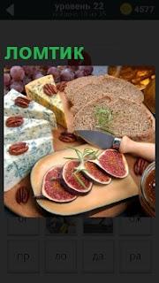 На столе ломтиками порезаны хлеб, сыр и фрукты, украшенные зеленью