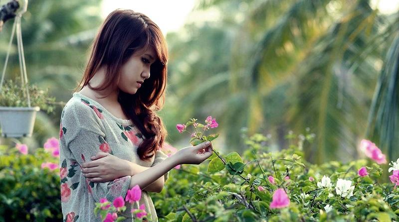 Jovem contemplando flores em um jardim