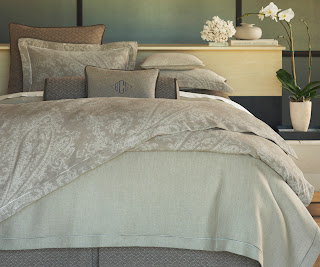 Luxury bedding in earthy neutrals with a rich paisley print and monogramming