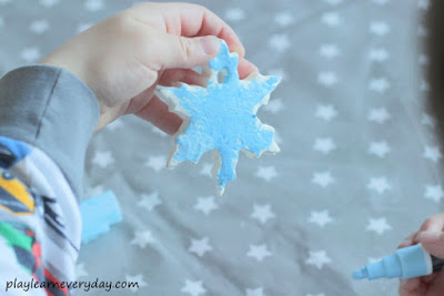 holding up a clay snowflake