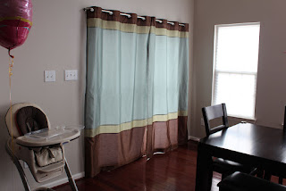 simplistic curtain drapes sliding glass door and double hung windows mixed with black dining table