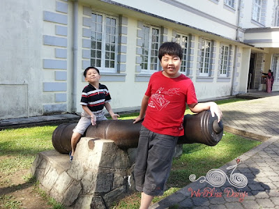 The boys sitting on the canon at Kuching Muzium