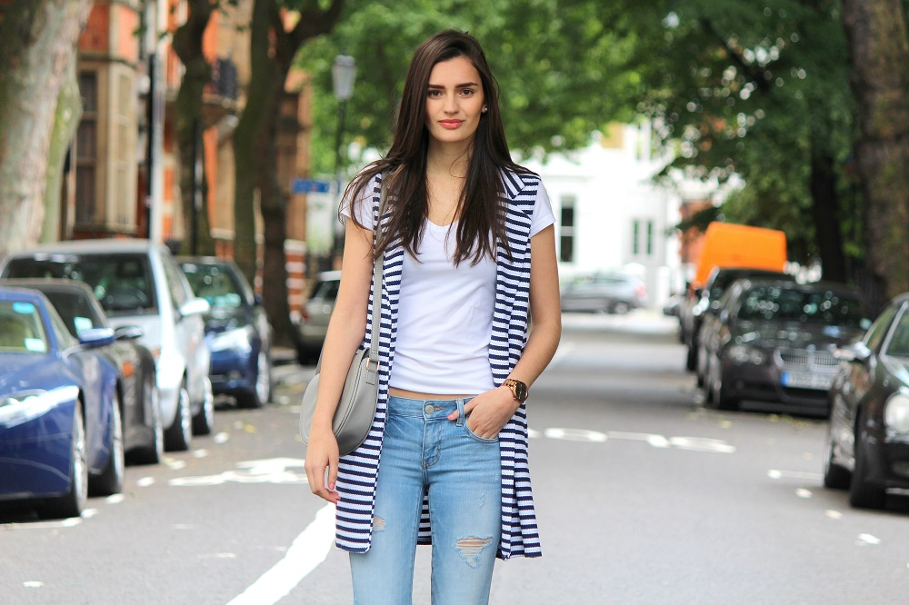 peexo fashion blogger wearing white tshirt and ripped jeans and striped sleeveless vest