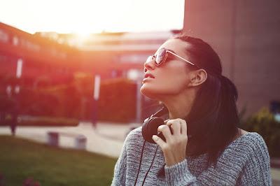 Chica fon gafas y cascos mirando al cielo con sol y edificio de fondo