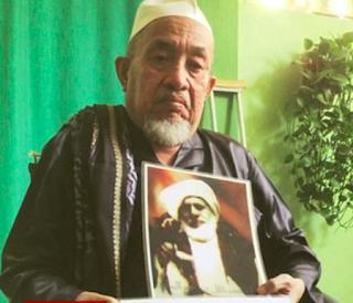 KH. Zubair Muntashar, Sedang Memegang Foto Syaichona Kholil