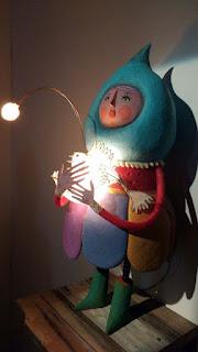 (descrição da imagem) Na foto colorida e vertical, uma boneca de papel machê colorido, suavemente iluminada, está em pé, voltada para a esquerda, sobre uma pequena superfície de ripas de madeira rústica afixada a uma parede branca. Uma grande gota azul clara envolve sua cabeça inteira, deixando de fora apenas o rosto redondo e rosado, de olhos miúdos e verdes, bochechas coradas e boca arredondada. Segura junto ao peito, entre seus braços muito compridos e fininhos e mãos de dedos delicados, um peixe branco e iluminado, com a bocarra de dentes afiados aberta. Da testa do peixe sai uma haste longa e curva que tem na ponta uma lâmpada acesa em forma de bolota. A boneca tem a silhueta arredondada e usa um vestido de gola branca com o peito e as mangas vermelhos e a saia em formato de pétalas largas, uma roxa, outra azul e outra, ainda, amarela. Suas pernas também são fininhas e ela está de meias listradas em branco e preto e galochas verdes. (fim da descrição) Foto: Kemi Oshiro.