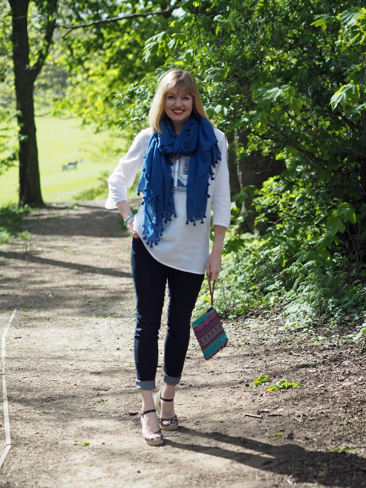 Embroidered white top with skinny jeans, a blue pompom scarf and espadrilles