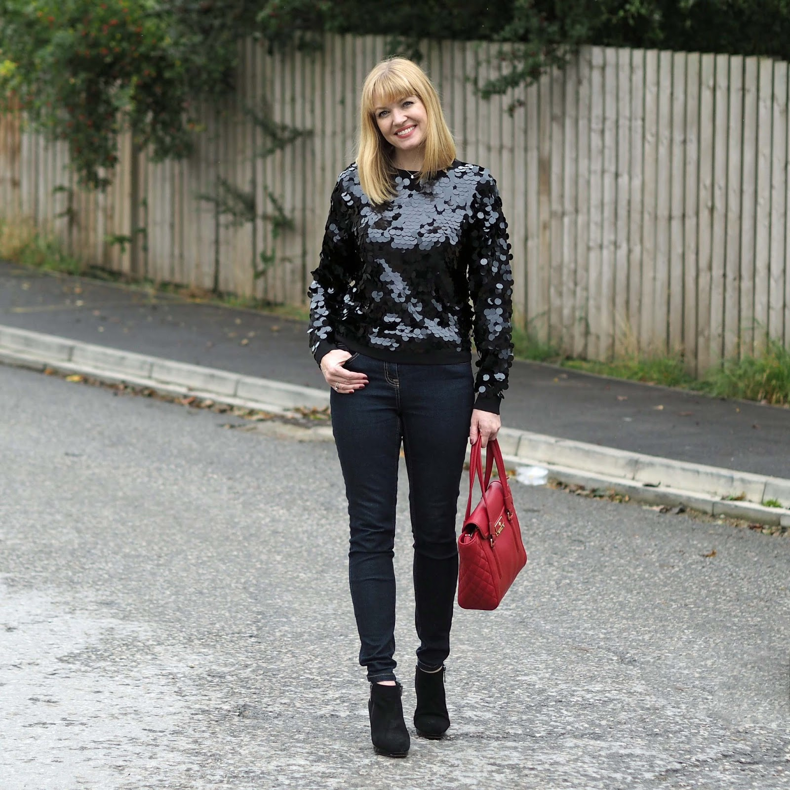 Black sequin sweater, sweatshirt, skinny jeans and red leather quilted Ilex tote bag