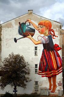 A foto mostra um gigantesco grafite na parede lateral de um prédio. O grafite à direita é de uma garota ruiva com trancinhas e traje típico polonês: Vestido regata com corpete preto, saia listrada em tons de vermelho, azul, amarelo e branco. O vestido tem um grande laço vermelho na cintura e está sobre uma camisa branca de mangas curtas bufantes com bordados. A garota parece flutuar, está descalça, na ponta dos pés regando uma árvore natural à esquerda, junto à parede do prédio.