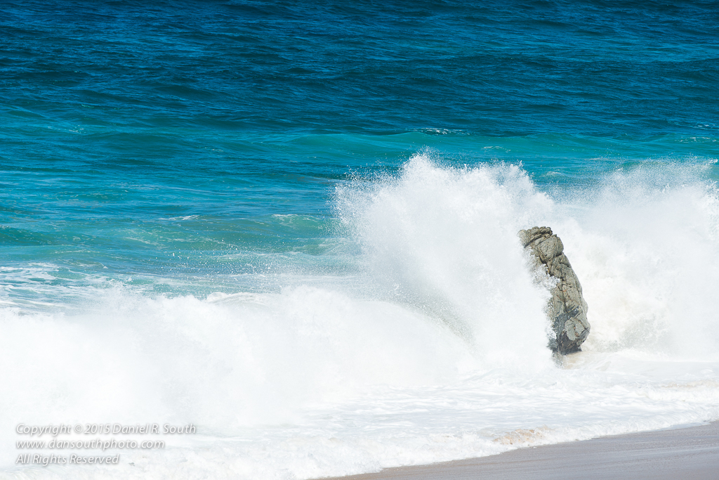 a photo of a rock being pounded by massive waves in the pacific ocean by daniel south