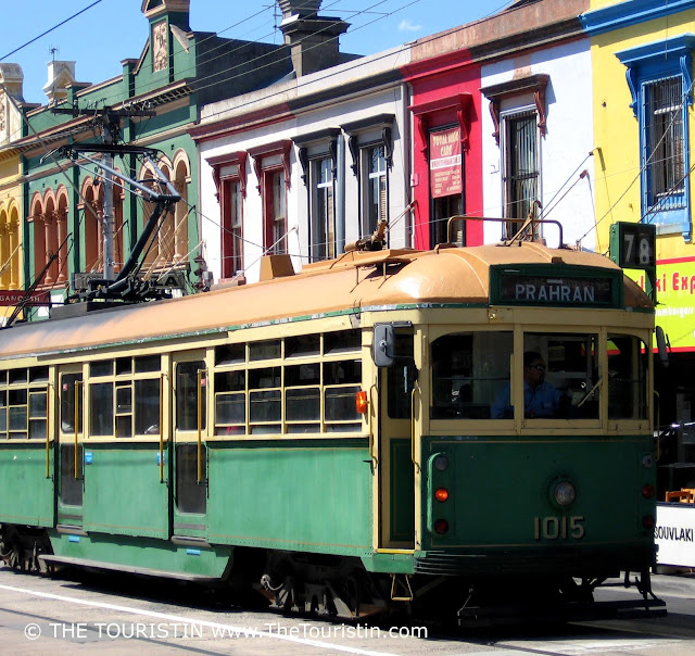 A green tram in front of a row of colourfull period houses.
