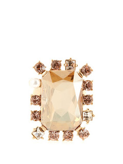 Oscar de la Renta's sparkling cocktail ring has been made from gold plated pewter in the USA. The stone in the centre is a Swarovski surrounded by smaller crystals and pearls. This ring is bold and feminine with a romantic twist.