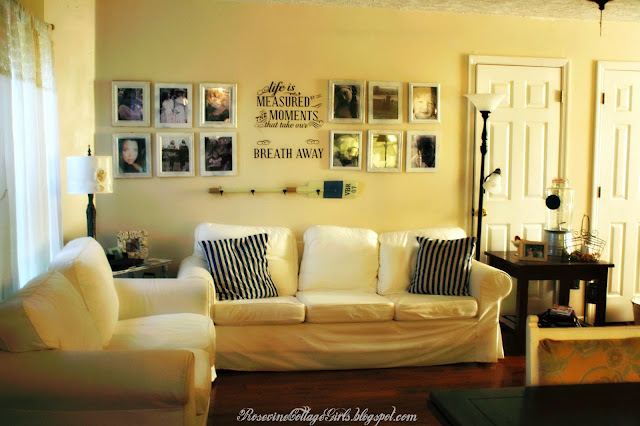 white couches with navy and white striped pillows and family photos on the wall | sea side living room | rosevinecottagegirls.com