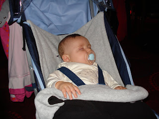 Baby Boy asleep in his pram in the noisy Holiday Club
