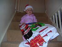 Top Ender sitting on the stairs having givenup taking her Christmas Sack upstairs