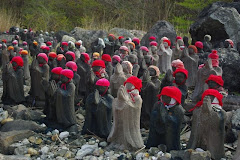 Praying statues with red hats
