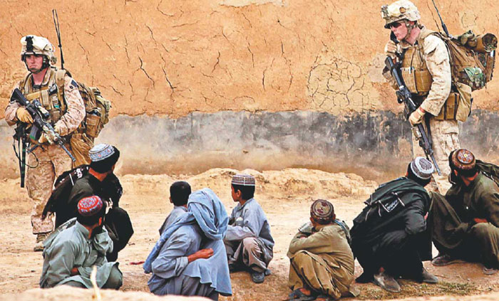 Occupation soldiers stand around a group of Afghan civilians,