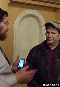 Rabbi Yisrael Pinson shows the Chabad website to a guest at the Detroit Chabad House in Detroit.