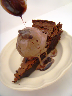 Spoon pouring sauce on ice cream topped chocolate cake.