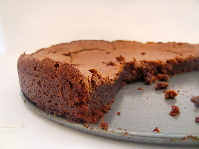 A pan with half flourless chocolate brownie cake on it.