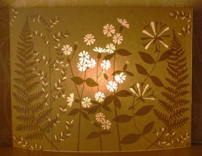 paper cut floral wall panel with light behind it