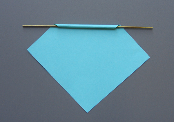 rolling a paper square on a sturdy wire to make a spill