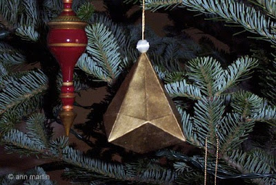 Folded paper German Bell Ornament hanging on Christmas tree along with a red wooden ornament
