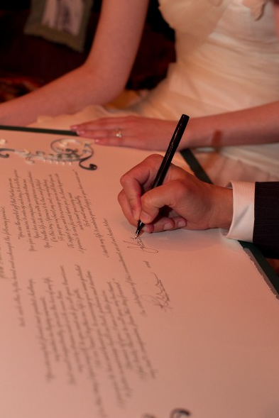 Quilled marriage certificate being signed by bride and groom
