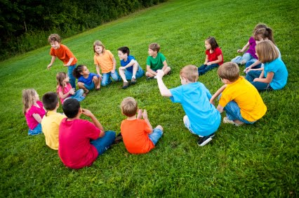 NAMC Montessori outdoor environment cosmic education peace. Children in a circle playing a game