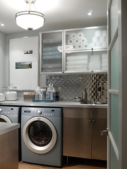Beautiful laundry room with stainless cabinets and backsplash by Sarah Richardson