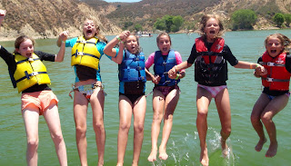 Aloha Beach Camp girls jumping off the back of a boat for a swim in Castaic Lake near Los Angeles, California.