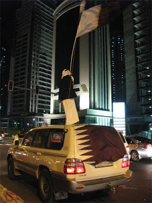 Standing on top of a car with a Qatar flag on Qatar National Day