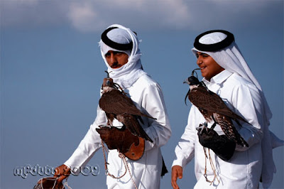 Two young arab men with their hawks.