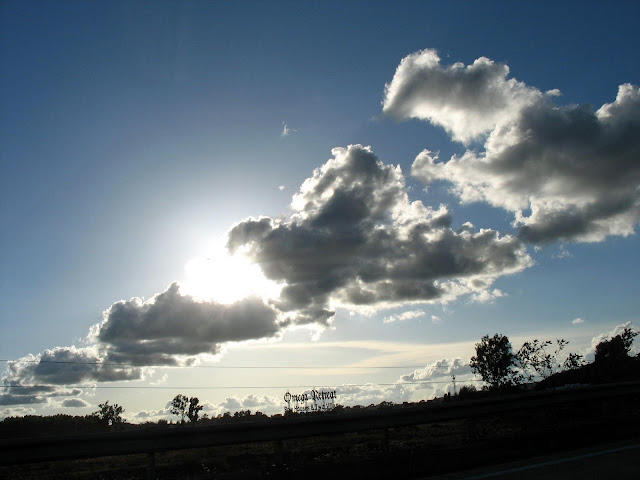 scene of sun, clouds and earth silhouette