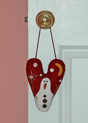 an assortment of ornaments are scattered on knobs throughout the house, including this wool felt snowman that I made in 2005