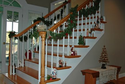 small Santas line the main stairway underneath pine rope garland, while a brown silk thread tree rests on the hallway bench