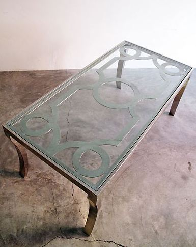 Iron coffee table with loop detaling and a glass top