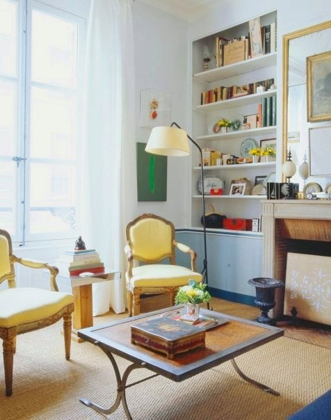 Living room in a Paris apartment with yellow Louis XIV chairs, a sisal rug on a wood floor, a coffee table with metal legs and a wood top, fireplace and built in bookshelves