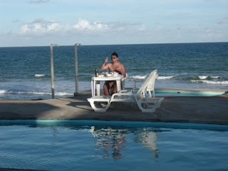 Piscina e pessoa comendo na mesa em frente à praia de Arembepe